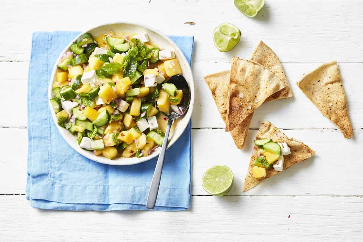 A bowl of salad with diced Qukes, diced mango, feta cheese and mint salsa.
